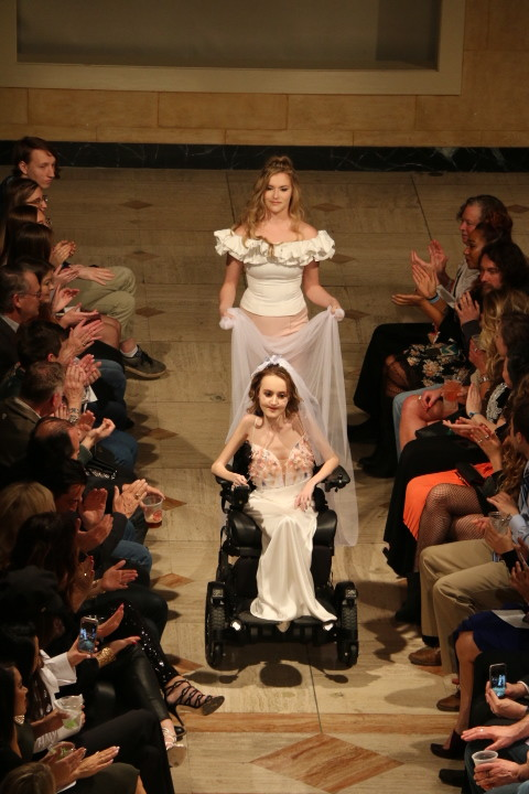 Designer Tobie Marie carries the veil of the model closing the show as the crowd applauds.