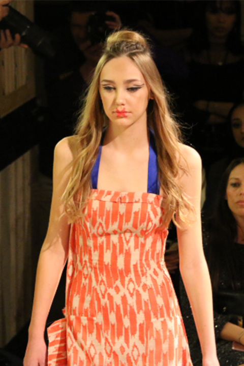 A vibrant ikat print in a vivid orange helps this flowy dress stand out on the runway.