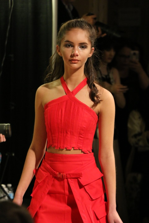 In red from head to toe, a model wearing Miranda Hanson's designs walks toward the cameras at the end of the runway.