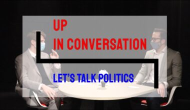 "Kody and Matt sit at a table talking. A transparent logo for ""UP in Conversation: Let's Talk Politics"" overlays the image."