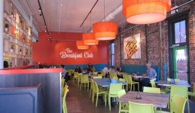 """front view of dining room, orange back wall with """"The Breakfast Club"""" written, customers eating at tables."""