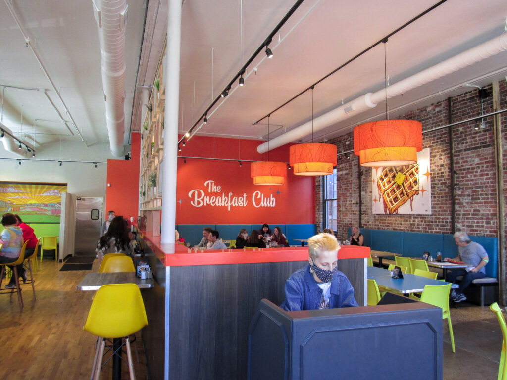 """host working at host stand, customers eating in dining room, orange back wall with """"The Breakfast Club"""" written across it."""