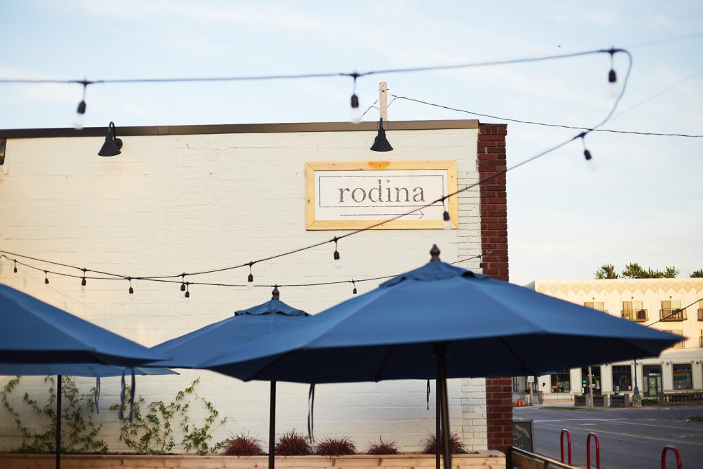 view of white brick wall and Rodina sign from patio outside the restaurant