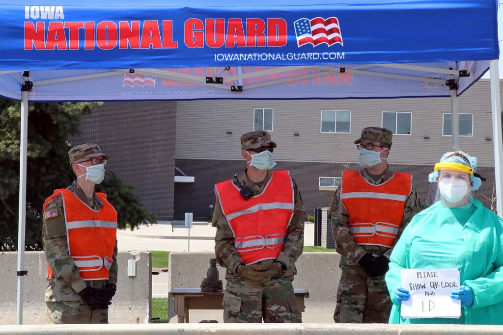 Three members of the Iowa National Guard and a nurse stand at a Test Iowa site.